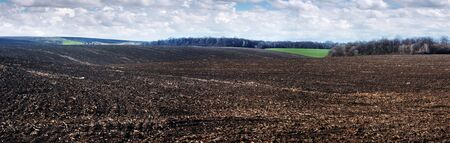 panoramic view of plowed field and a field of winter wheat in the hilly terrain with cloudly sky Banco de Imagens