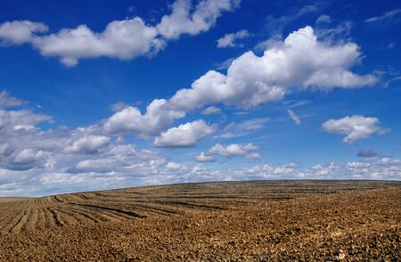 panoramic view of plowed field in the hilly terrain with cloudly sky Banque d'images