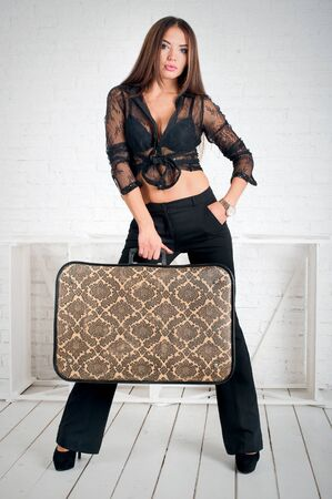 glamorous brunette stands in flared pants, top t-shirt with retro suitcase in hands on light background