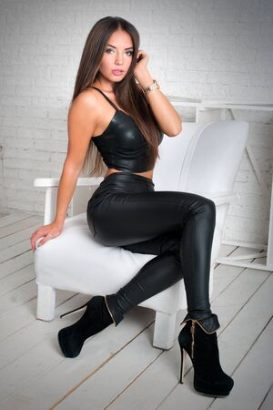 glamorous brunette sitting in leather tight trousers, top on light background, fashion