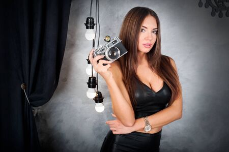 glamor brunette in leather clothes holding retro camera in the hands on light bulb background