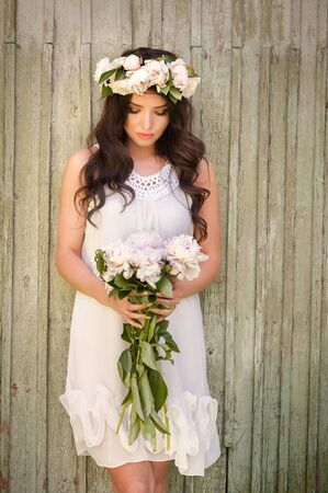 portrait of young lady with spring wreath and bouquet of peonies in hands and rustic wood background