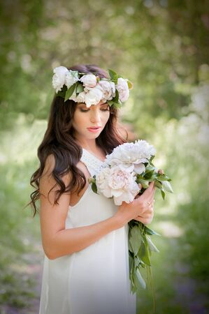 beauty girl with spring wreath and bouquet of white peonies in hands, light dress