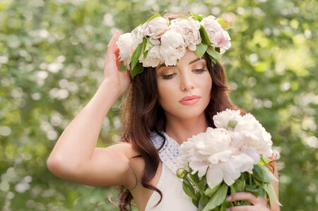 young women with spring wreath and bouquet of white peonies in hands