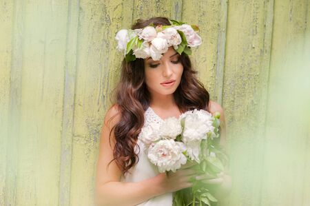portrait of lady with spring wreath and bouquet of peonies in hands and blurred rustic wood background