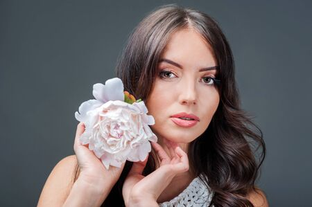 portrait of young brunette woman with peony flower in her hands on grey background Banque d'images