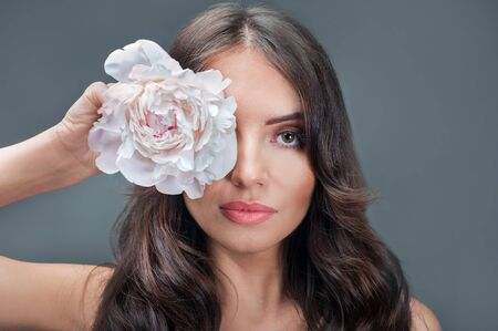 beauty portrait of young brunette, cover her eyes with a flower peony on grey background