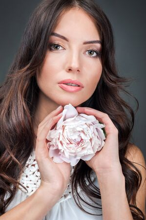beauty portrait of young brunette with peony flower in her hands on grey background Banque d'images