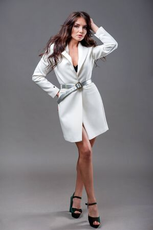Beautiful girl posing in trendy white raincoat, makeup isolated on gray background. spring fashion