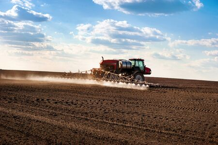 self-propelled sprayer in the field makes fertilizers in early spring, backlit jet