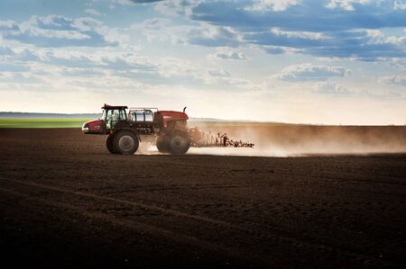 a self-propelled sprayer in the field cultivates arable land against the light