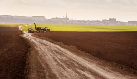 Big sprayer in the arable field at refueling in early spring , view with evening warm light