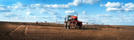 Panoramic view of self-propelled red sprayer in the field makes fertilizers in early spring