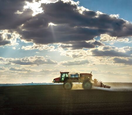 a self-propelled sprayer in the field cultivates arable land against the fantastic light from under the clouds Banque d'images