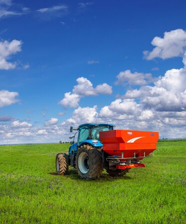 blue tractor in field work with modern red two-disc fertiliser spreader sprayer