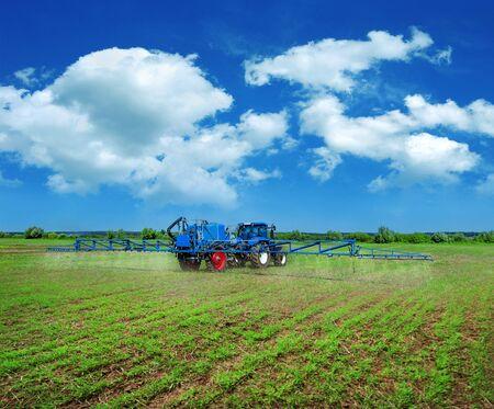 new blue tractor in field work with trailed sprayer, winter crop fertilizers, spring crop fertilizers, beautiful sky