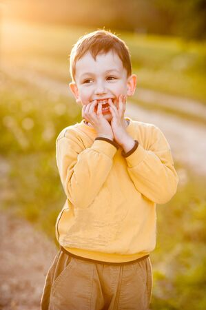 Happy little boy laughs, yellow warm evening light, childhood illustration