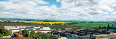 panorama of borders city with Arable lands' blooming rapefield of village near