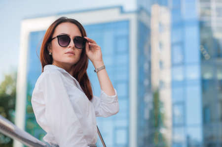 Young beautiful business woman with glasses at street