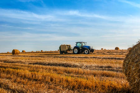 A tractor uses a trailed bale machine to collect straw in the field and make round large bales