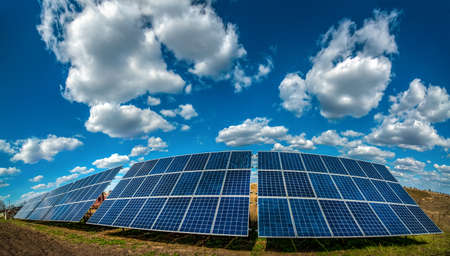 Solar energy station panel system on plowed field and sky with beautiful clouds Archivio Fotografico