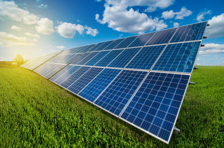 Solar energy panel system power at green grass and sky with clouds and sunshine Archivio Fotografico