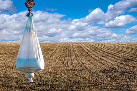 bag of seeds or mineral fertilizers at crane on field with stubble