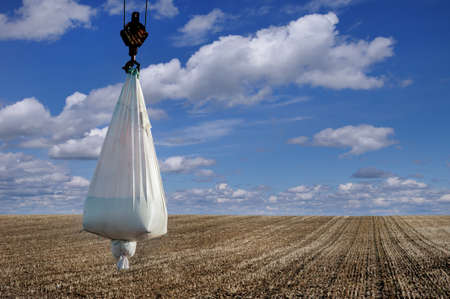 bag of seeds and mineral fertilizers at crane on field before sowing, beautiful clouds and sky