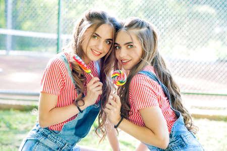 Portrait of two beautiful girls twins with lollipop caramel Stock Photo