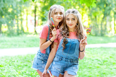 two beautiful twin girls in denim overalls with lollipops