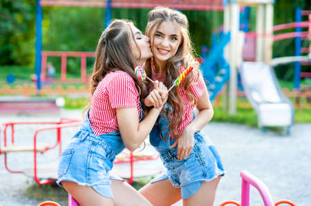 two happy twin sisters laughing and kissing in denim overalls with lollipops on the playground