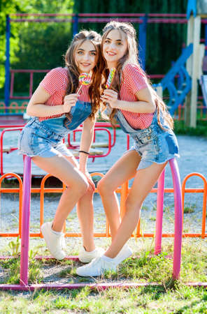 two beautiful twin sisters laughing in denim overalls with lollipops on the playground Stock Photo