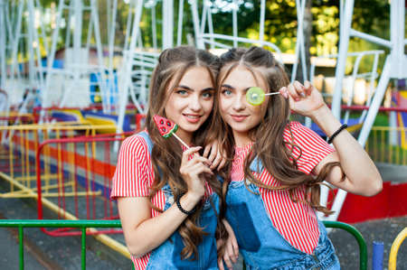 teen twin sisters in colorful clothes with lollipops caramel with colorful swing on background