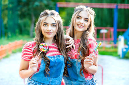 Beautiful teenage twins sisters with colorful lollipops