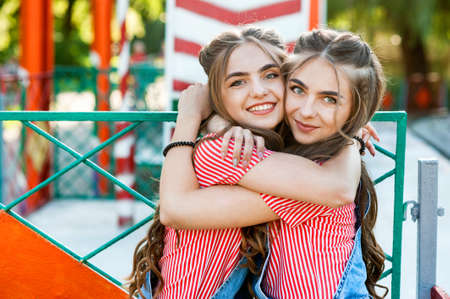 Beautiful teenage twin sisters in colorful clothes with lollipops hugging