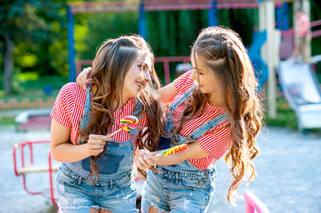 two happy twin sisters laughing in denim overalls with lollipops on the playground