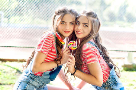 Portrait of two beautiful girls twins with lollipop Stock Photo