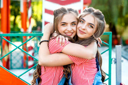 two beautiful twin girls hugging in denim overalls with lollipops