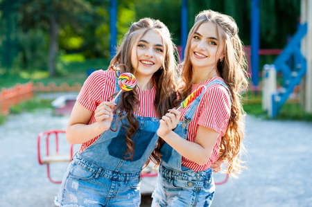 two beautiful twin girls hugging and laughing in denim overalls with lollipops