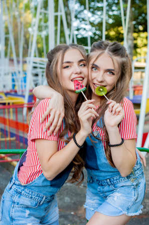 Beautiful teenage twin sisters in colorful clothes with lollipops caramel on colorful swing background