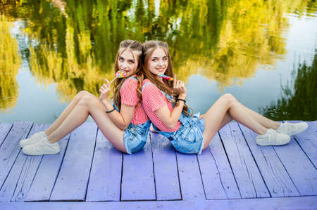 Beautiful teenage twin sisters in colorful clothes with lollipops sitting on colored boards Stock Photo