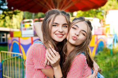 teenage twin sisters in colorful clothes embracing, happy emotions, with colorful swings on background