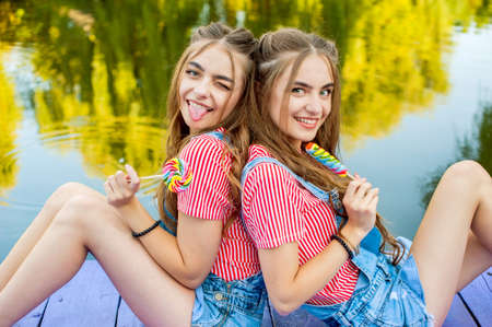 Beautiful teenage twin sisters in colorful clothes with lollipops sitting on colored boards by the pond