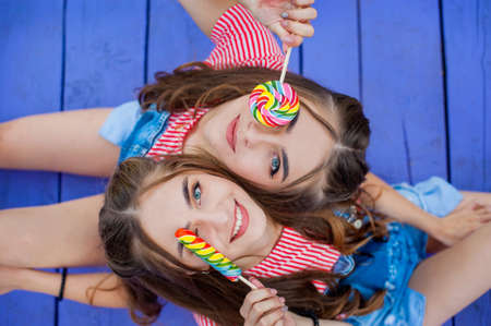 Beautiful teenage twin sisters in colorful clothes with lollipops sitting on colored boards top view