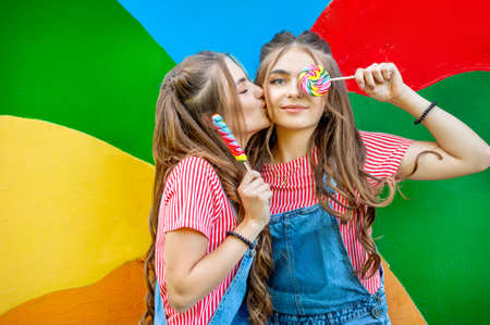 Beautiful teenage twin sisters in colorful clothes with lollipops on a colorful background