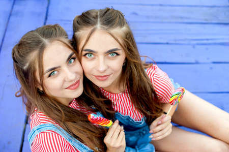 Beautiful teenage twin sisters in colorful clothes with lollipops sitting on colored boards, top view Stock Photo