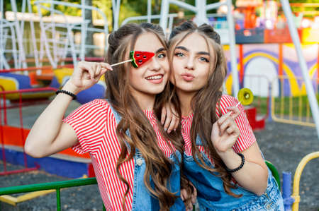 teenage twin sisters in colorful clothes with lollipops, joy emotions on colorful swing background Stock Photo