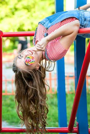 lovely teen girl in denim overalls with lollipop hanging upside down