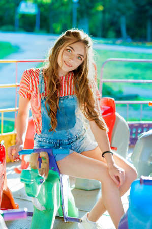teen girl in colorful clothes embracing, sitting on a swing