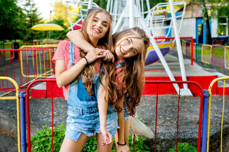 twin sisters in colorful clothes embracing, happy emotions, with colorful swings